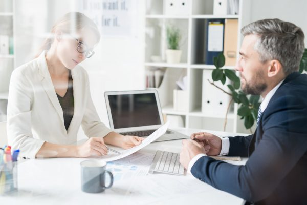 Financial adviser analyzing papers with businessman