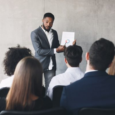 Top manager showing chart to colleagues, making presentation
