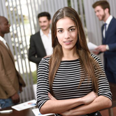Businesswoman leader looking at camera in working environment.