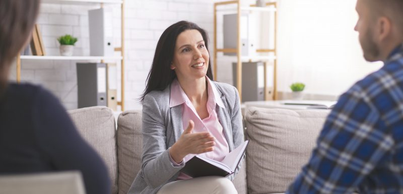 Professional psychologist giving advice to newlyweds at session